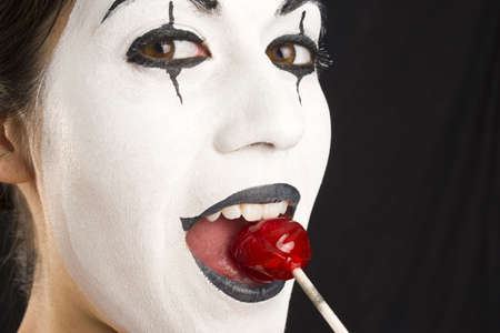 whites: A Mime enjoys a lollipop in an up close portrait. Stock Photo