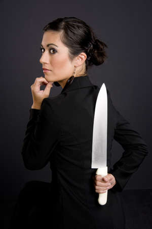 hides: Pretty Woman hides a big knife Stock Photo