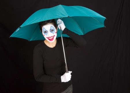 A happy clown shelters under a colorful umbrella