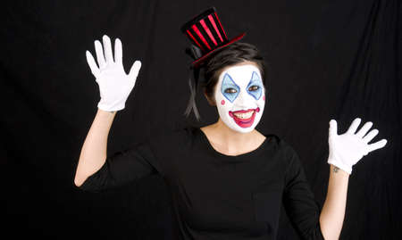 Woman clowning around against black Stock Photo