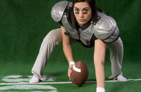 crouches: A woman crouches in a football pose as a center Stock Photo