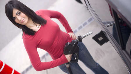 gas nozzle: A woman at the gas station