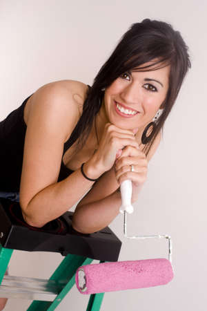 A beautiful brunette home maker prepares to paint a room in her home photo
