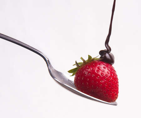 Chocolate sauce hits the berry on a spoon photo