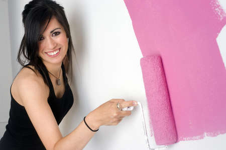 A brunette woman paints the wall of her apartment Stock Photo