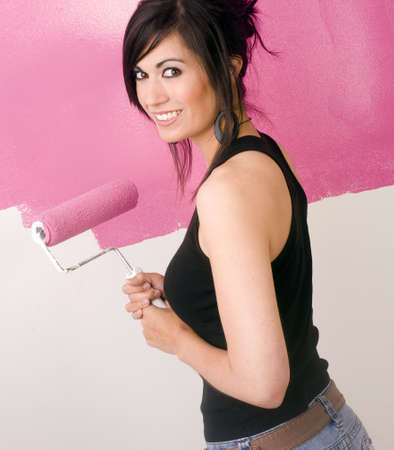 A brunette woman paints the wall of her apartment photo