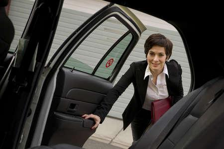 taxi: Una mujer de negocios se mete en la cabina