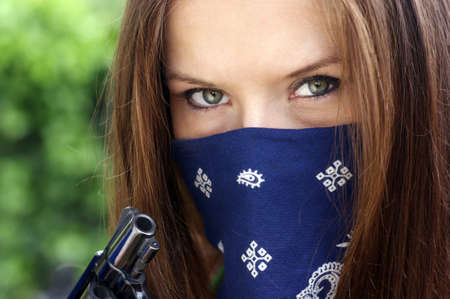 A woman holds a revolver with a bandanna over her face