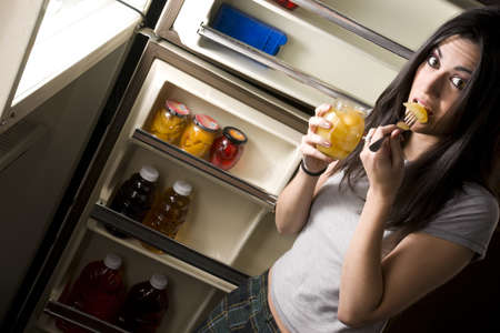 A sleepy woman lingers at the refrigerator door and gets suprised when you catch her photo