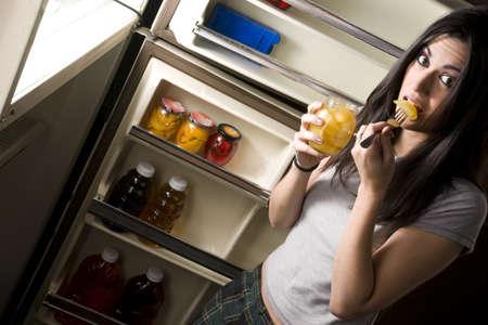 merenda: Una donna sonnolenta indugia alla porta del frigorifero e viene sorpreso quando la sua cattura