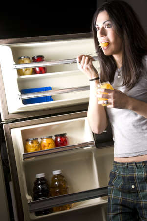 A sleepy woman lingers at the refrigerator door for a snack photo