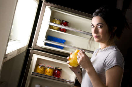 A sleepy woman lingers at the refrigerator door and gets suprised when you catch her nibbling outside her diet plan Stock Photo