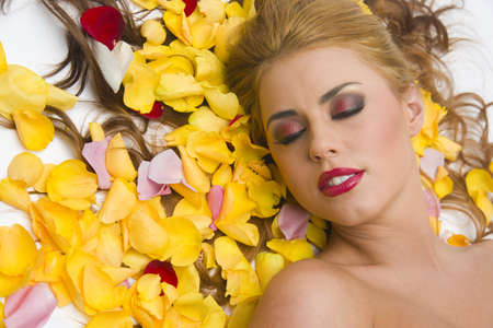 Beautiful woman lays in a pile of rose petals Stock Photo - 15512255
