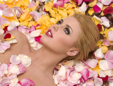 Beautiful woman lays in a pile or rose petals Stock Photo - 15512252