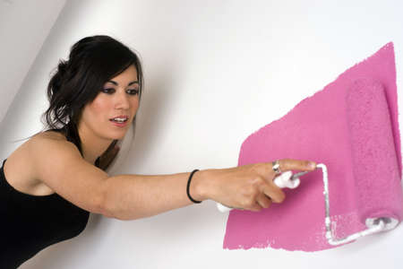 A beautiful woman paints the wall pink
