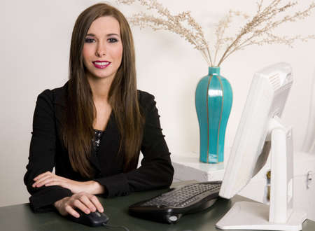 A pretty receptionist smiles at the viewer Stock Photo - 15649330