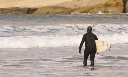A lonely surfer heads back out in a full wet suit photo