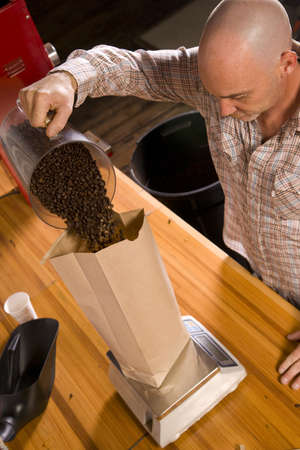 An experienced coffee roaster bags up his finished product  스톡 콘텐츠