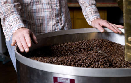 producing: A coffee roaster labors over the cooling bin Stock Photo