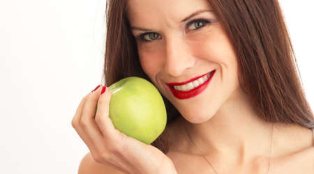 Stunningly beautiful young woman in a head and shoulders looks right at you holding an apple Stock Photo - 15892646