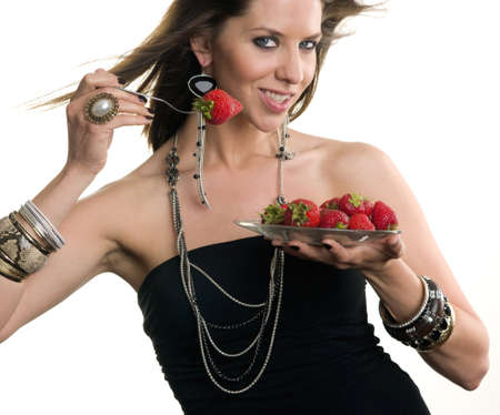 Woman eats Strawberry with a fork photo