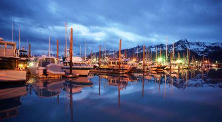 The Seward Marina stand before a beautiful mountain range at night 스톡 콘텐츠