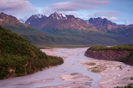 A riverbed flows by a beautiful mountain range
