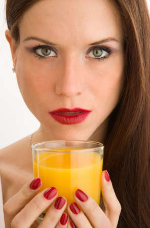 Colorful Womans hand holds a glass of Orange Juice