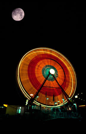 blurr: A fair ride at night with full moon Stock Photo