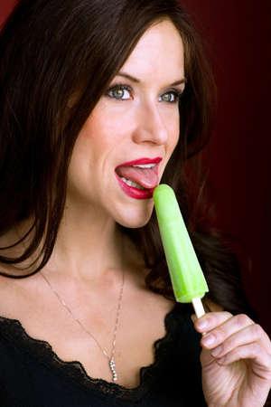 A beautiful brunette has a frozen treat looking off camera