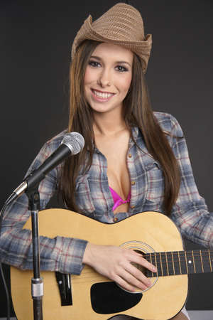 Attractive woman in the studio with her guitar photo