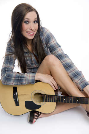 Attractive woman in the studio with her guitar Stock Photo - 16682530