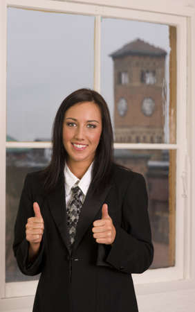 An attractive woman smiles and indicates thumbs up photo