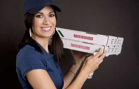 A stunning brunette woman brings pizza and a smile via delivery photo