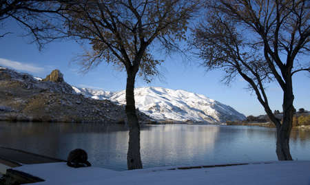 Winter Snow on the Peaceful Columbia River under the trees looking at a rock butte photo