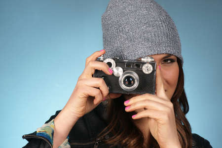 Hip Attractive Woman in Beanie Cap Snaps a Picture of Viewer with Vintage Camera photo