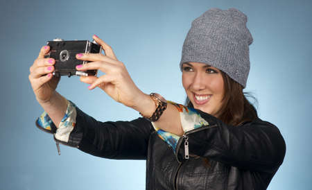 Hip Attractive Woman in Beanie Cap Snaps a Picture of Herself with Vintage Camera photo