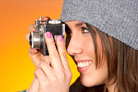 Hip Attractive Woman in Beanie Cap Snaps a Picture with Vintage Camera photo
