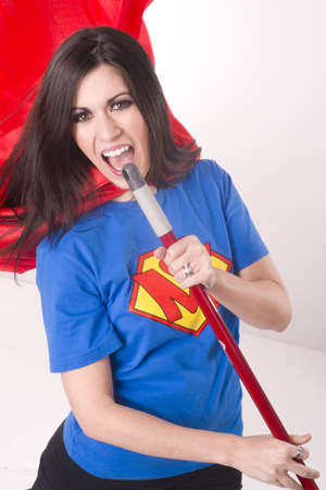 A beautiful woman in crested shirt and red cape lipsyncs with her broom stick while cleaning