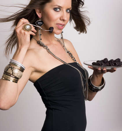 Female wearing accessories enjoys some whole fruit photo