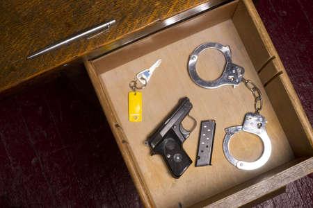 restraints: A desk housing pen, gun, key, and handcuffs Stock Photo