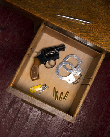 restraints: A desk housing pen, a key, ammunition, and handcuffs