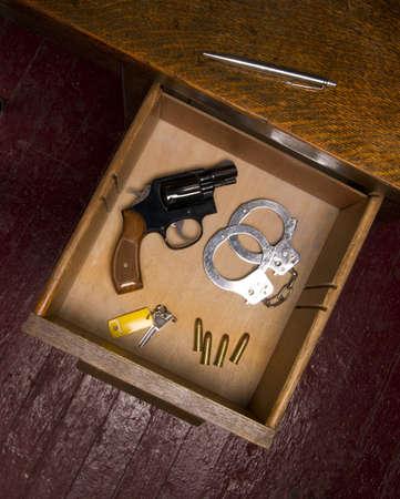 restraints: A desk housing pen, a key, ammunition, and handcuffs