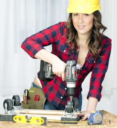casters: A Female works on a repair project in the shop Stock Photo