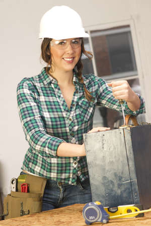 A Female works on a repair project in the shop photo