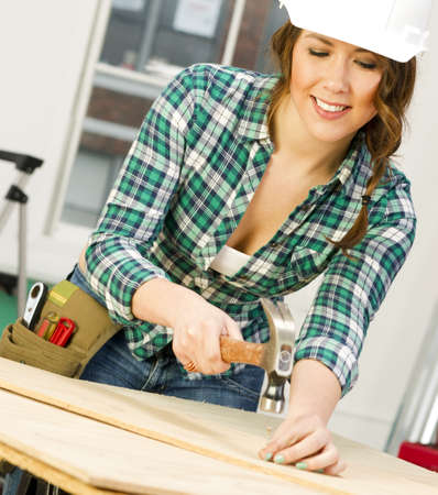 A Feamle works on a repair project in the shop Stock Photo