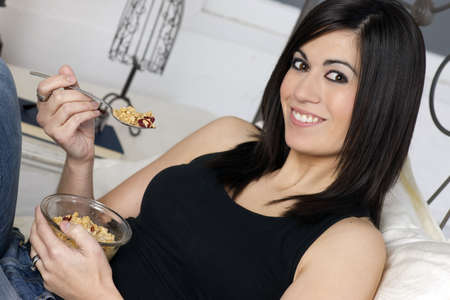 A horizontal composition of a woman eating cereal Stock Photo - 18200448