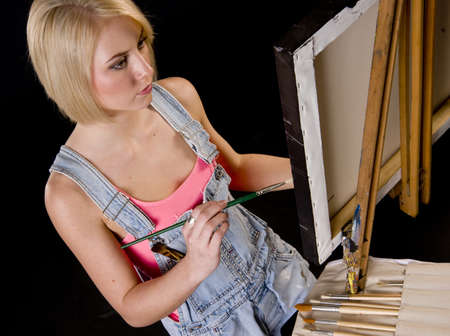 finishing touches: A Happy Blond Woman Dressed in Overalls Provides Finishing Touches to Painting on Easel