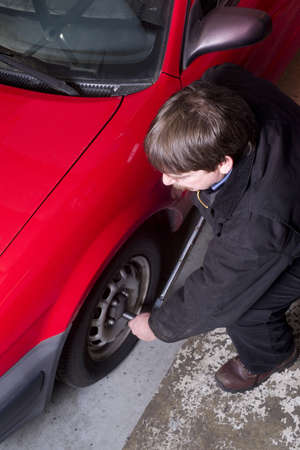 Uniformed Auto Technician Uses Breaker Bar Loosening Lug Nuts on Car Stock Photo - 18578199