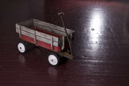 deteriorated: Vintage Rusted Red Metal Utility Wagon on Old Wood Floor Stock Photo